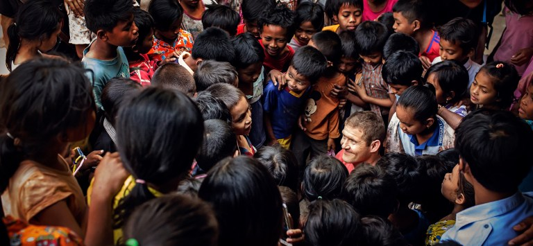 Swarmed by students Stepping Stones School Cambodia Photographers Capturing Inspiring Journey of a Man Without Arms and Legs